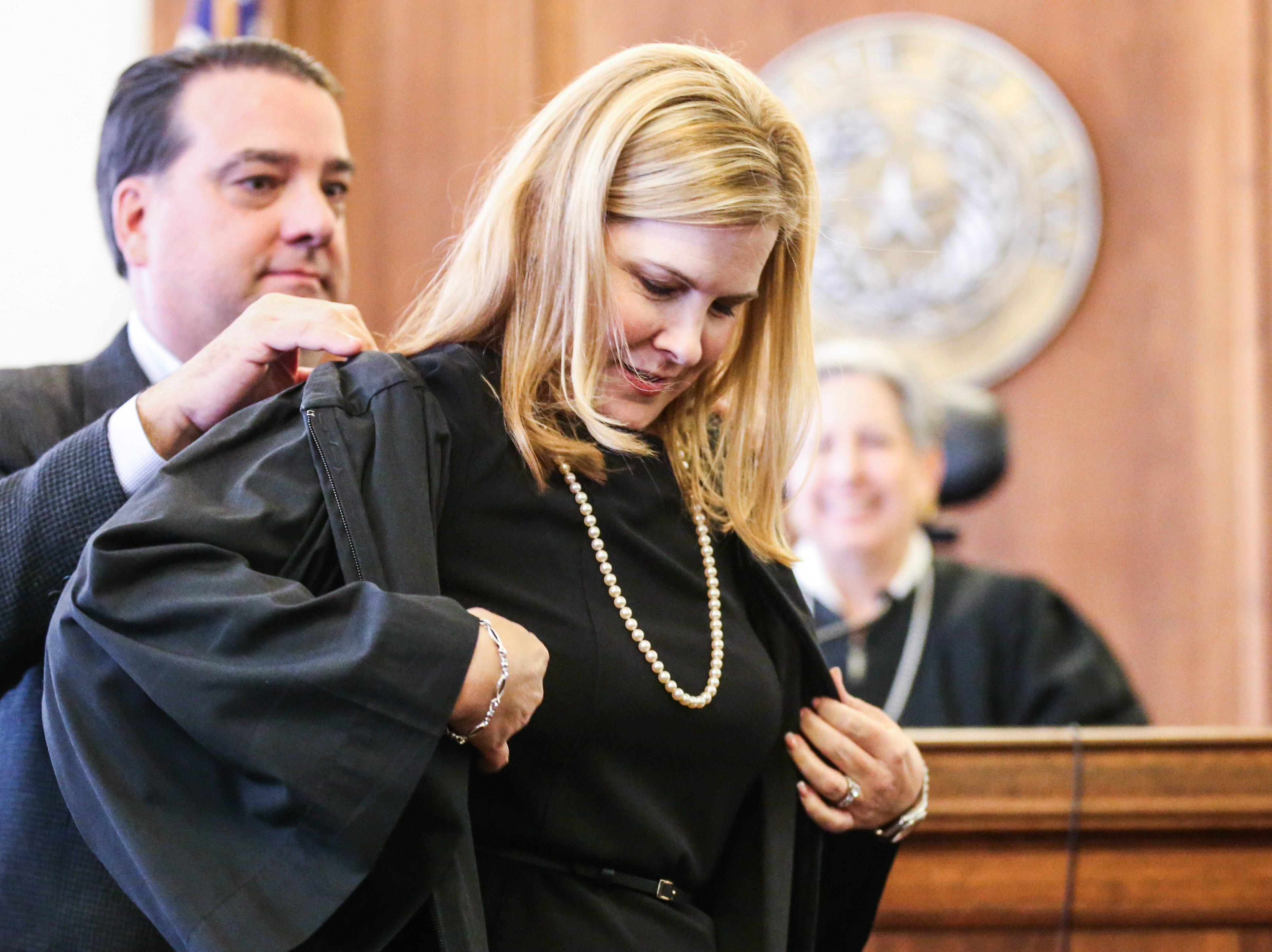 Judge Carmen Dusek puts on her robe after being sworn in as 51st District Court judge Friday, Dec. 14, 2018, at Tom Green Courthouse.