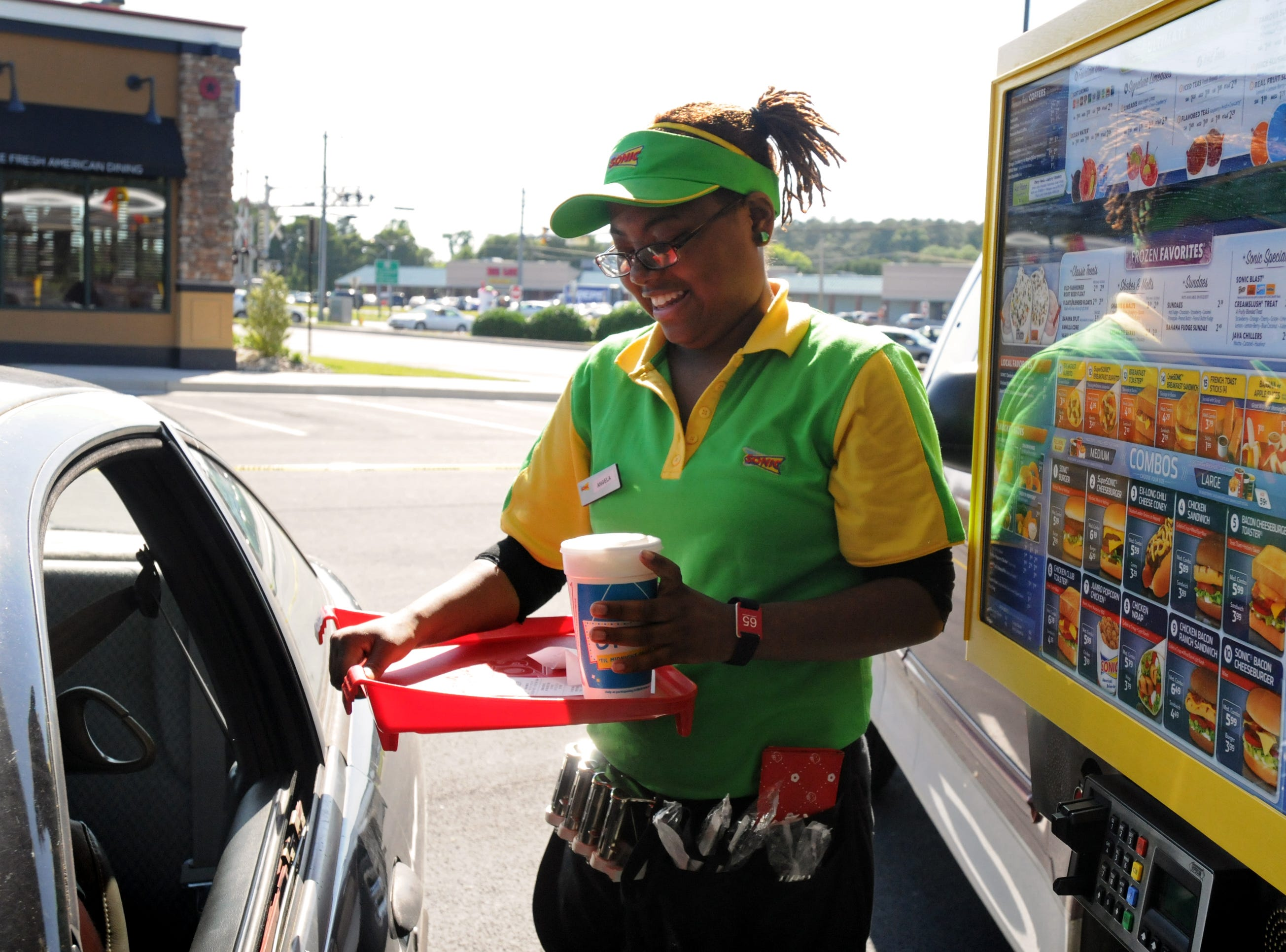 051909-- Laura Emmons photo-- Car-hop Angela Foreman of Salisbury delivers food to a car as customers flocked to the newly opened Sonic Drive-In in Fruitland on May 19, 2009.