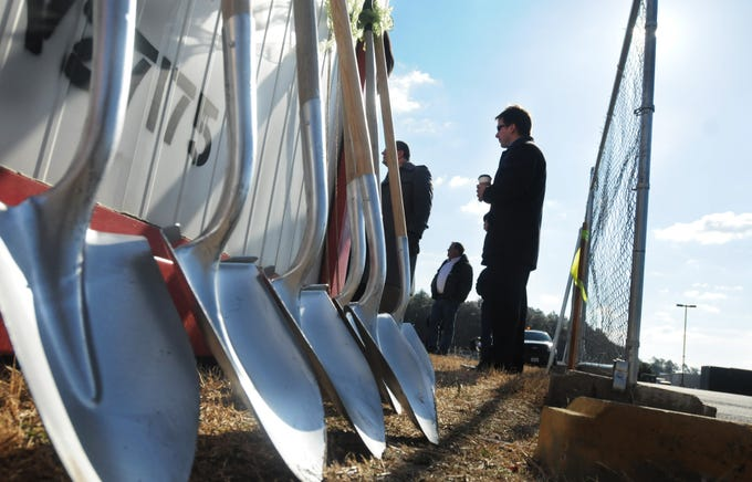 A line of shovels sit against a shed while Brad Gillis of Salisbury awaits the ground breaking ceremony for Sonic in Fruitland, Monday, Feb. 23, 2009.