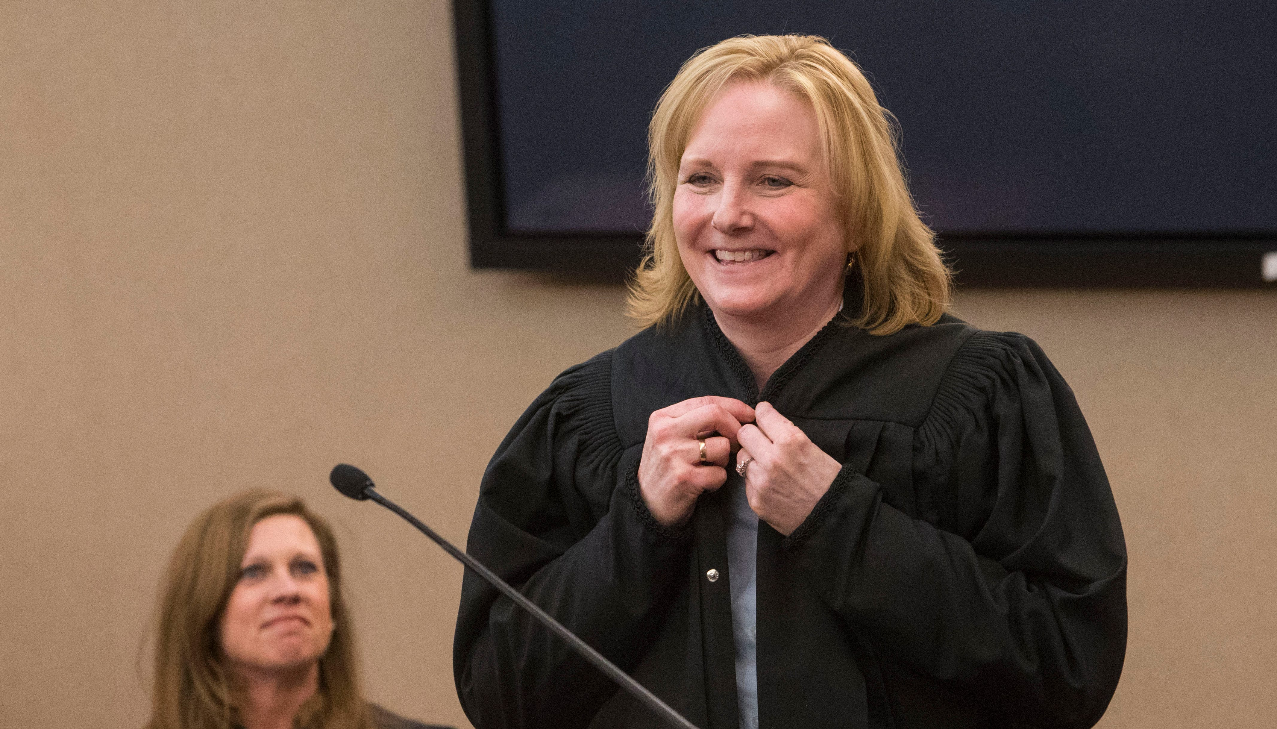 Sandra Hoglund Hanson puts on her robe after being sworn in as new circuit court judge at the Minnehaha County Clerk-Courts in Sioux Falls, S.D., Friday, Dec. 14, 2018.