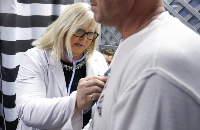 Tricia Derges listens to a patient's chest at the Lift Up Springfield medical clinic in 2018.