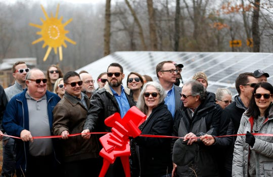 Visitors and board members and donors from the Watershed Committee of the Ozarks dawn sunglasses despite the overcast weather during a ribbon cutting for an array of solar panels at Valley Water Mill Park on Friday, Dec. 14, 2018.