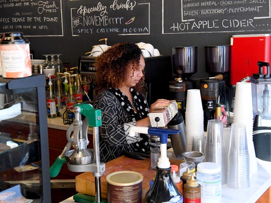 Mandisa Fullwood, owner of The French Press, works behind the counter preparing a customer's order at her business in Waynesboro on December 10, 2018.