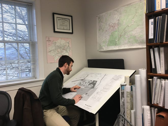 Waynesboro city planner Luke Juday uses a ruler as he views a map in his office. When developers approach him about a project, he makes sure it will fit the city's comprehensive plan.