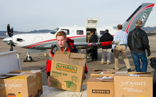 Scout Erik Ivester unloads a box of toys for Enoch Elementary School students at the Cedar City Regional Airport for the 18th annual Santa Flight Friday, December 14, 2018. The Santa Flight is sponsored by Angel Flight, a non-profit organization that provides non-emergency air travel for children and adults with serious medical conditions. Scouts working on their Eagle projects partnered with the Santa Flight to provide a toy for all of the 500+ students at the school.