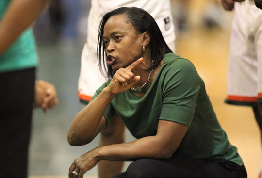FAMU DRS boys basketball coach Dione Desir directs her team during a timeout in a game against St. John Paul II on Dec. 4, 2018.