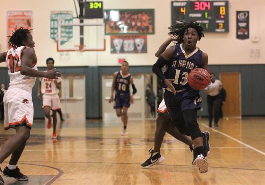 St. John Paul II junior Tyreke McElwain drives to the basket as the Panthers beat FAMU DRS on Dec. 4, 2018.
