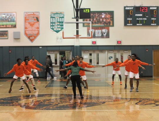 FAMU DRS boys basketball coach Dione Desir takes her team through a warm-up drill prior to the Rattlers playing St. John Paul II on Dec. 4, 2018.