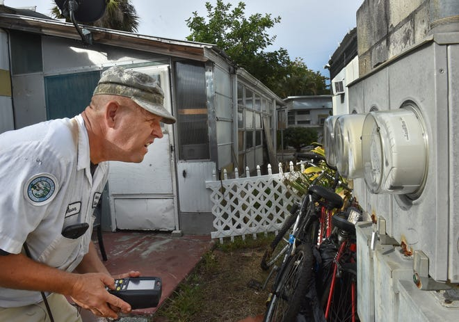 """City of Vero Beach meter reader Jason Cranman logs the data by hand from a series of electric meters at the Vero Mobile Home Park on Friday, Dec. 14, 2018, in Vero Beach. Friday is the last day city meter readers will read the electric meters, but they will continue to read the city water meters. """"I'm just thankful I have a job still,"""" Cranman said. The city is expected to close the electric sale with Florida Power & Light Co. on Dec. 17."""