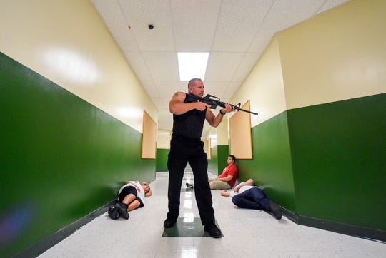 "Port St. Lucie Police Officer Chris Kneidel plays the part of an active shooter Wednesday, July 11, 2018, during ""active threat"" and S.A.V.E. (Swift Assisted Victim Extraction) training along with St. Lucie County Fire Rescue at Renaissance Charter School of St. Lucie in Port St. Lucie."