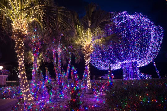 Visitors admire the lights illuminating the property at Robert and Elsa Eustace's Jensen Beach mansion Wednesday, Dec. 12, 2018, on Hutchinson Island. The Christmas lights are LEDs, according to longtime employee Hector Garza, who began decorating the property Oct. 15 with help from his crew. The lights can be seen at the mansion just north of Jensen Beach Causeway on A1A beginning at sunset every night through the holidays.