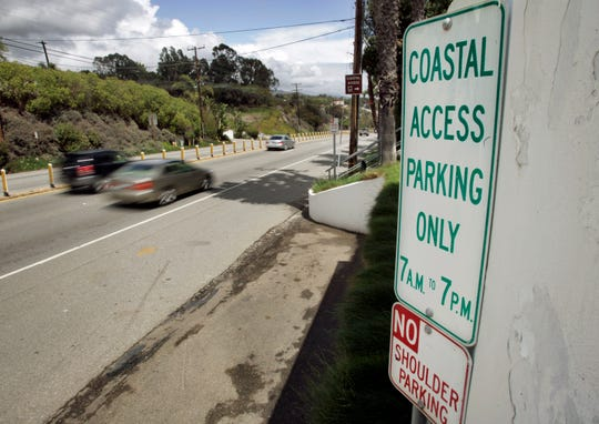In this April 20, 2007 file photo a sign directing visitors to two parking spaces next at a coastal access gate for Escondido Beach is shown on Pacific Coast Highway in Malibu. A new smartphone app that shows users a map of more than 1,500 access points along the California coast was created with help from a tech billionaire whose elaborate wedding ran afoul of state regulators.
