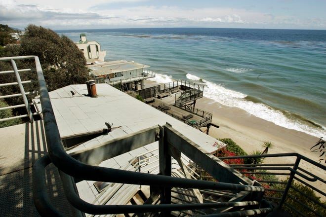 In this April 20, 2007 file photo beachgoers have this view of public beach and private residences from the top of a stairway access to Escondido Beach in Malibu. A new smartphone app that shows users a map of more than 1,500 access points along the California coast was created with help from a tech billionaire whose elaborate wedding ran afoul of state regulators.