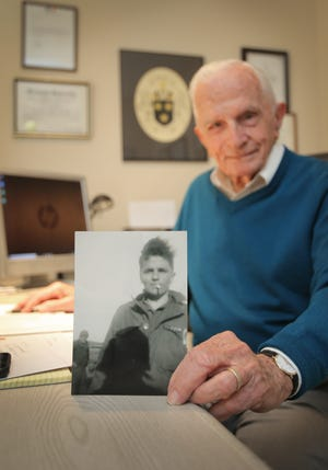 Jack Moran holds a picture of himself at 19 somewhere in Germany. He fought in World War II and participated in the famous Battle of the Bulge. At 93 years old, he is still working as a real estate agent for Coldwell Banker in Westlake Village.