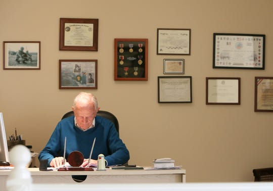 World War II Army veteran Jack Moran sits at his desk in his home in Westlake Village. Behind him on the wall are some of his accolades, letters, awards and certificates that he has received as a veteran and a survivor of World War II. At 93 years old, he is still working as a real estate agent for Coldwell Banker in Westlake Village.