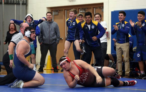 Mahopac wrestlers celebrate a pin by teammate Joe Harney against Fox Lane's Nino Prisco in the 285-pound weight class Thursday during the Division 1 wrestling dual meet championship at Mahopac High School.