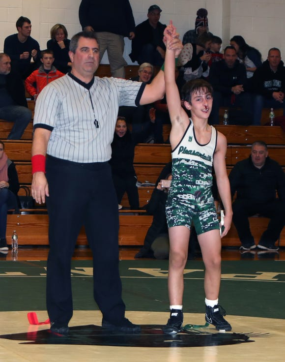 Official Ray Sarcone signals Pleasantville's Christian Perlleshi's win over Pearl River's Ian Rowan in the 99-lb match Thursday at the Division II wrestling dual meet championship at Pleasantville. Perlleshi got a bloody nose in the last seconds of the match.