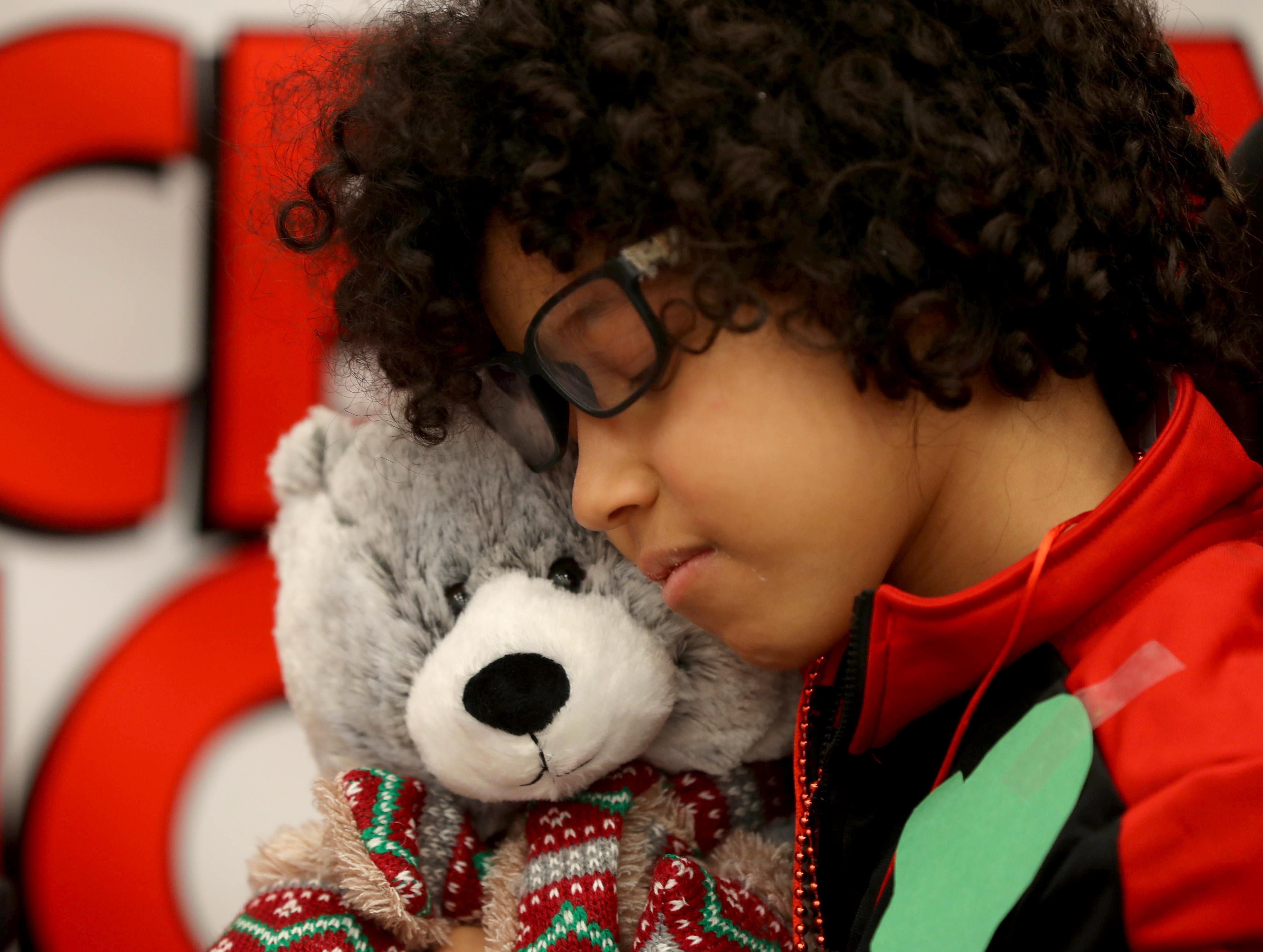 Rocky Marrero, 10, a patient at Blythedale Children's Hospital in Valhalla, cuddles with a stuffed bear during the annual holiday show at the hospital Dec. 14, 2018.