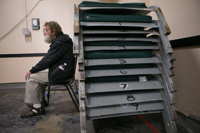 Sitting next to his walker and a pile of metal beds, Bill Rathmanner, 60, is homeless and living at SafeSpace Delaware in Wilmington.