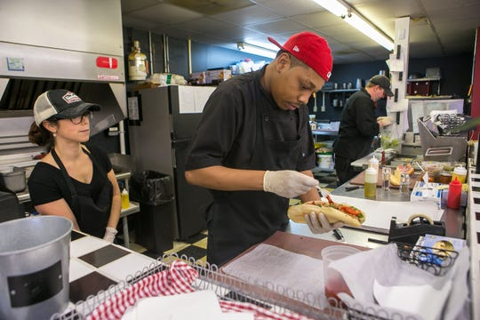 Mia Alcocer (left), Aaron Loweryberg  and owner Eric Huntley (right) cook up orders at Gaudiello's in Trolley Square.