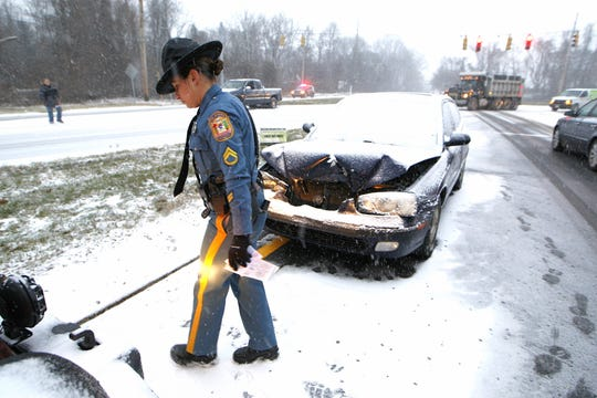 A Delaware State Trooper arrives on the scene where a sedan heading north on Newport Gap Pike and Lancaster Pike lost control from snow and ice conditions during a previous snowstorm.