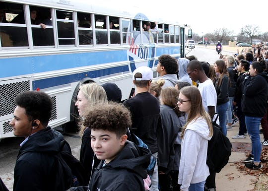 Students and family cheer on the Rider football players Friday, Dec. 14, 2018, as they leave school to head to AT&T Stadium for their Class 5A Division II semifinal game against Aledo.
