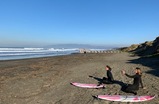 Surfers Andrea Moller, left, and Bianca Valenti, get ready for a practice session at Ocean Beach in San Francisco. Both will compete at Mavericks, a big wave competition that is allowing women in for the first time, and giving them equal prize money.