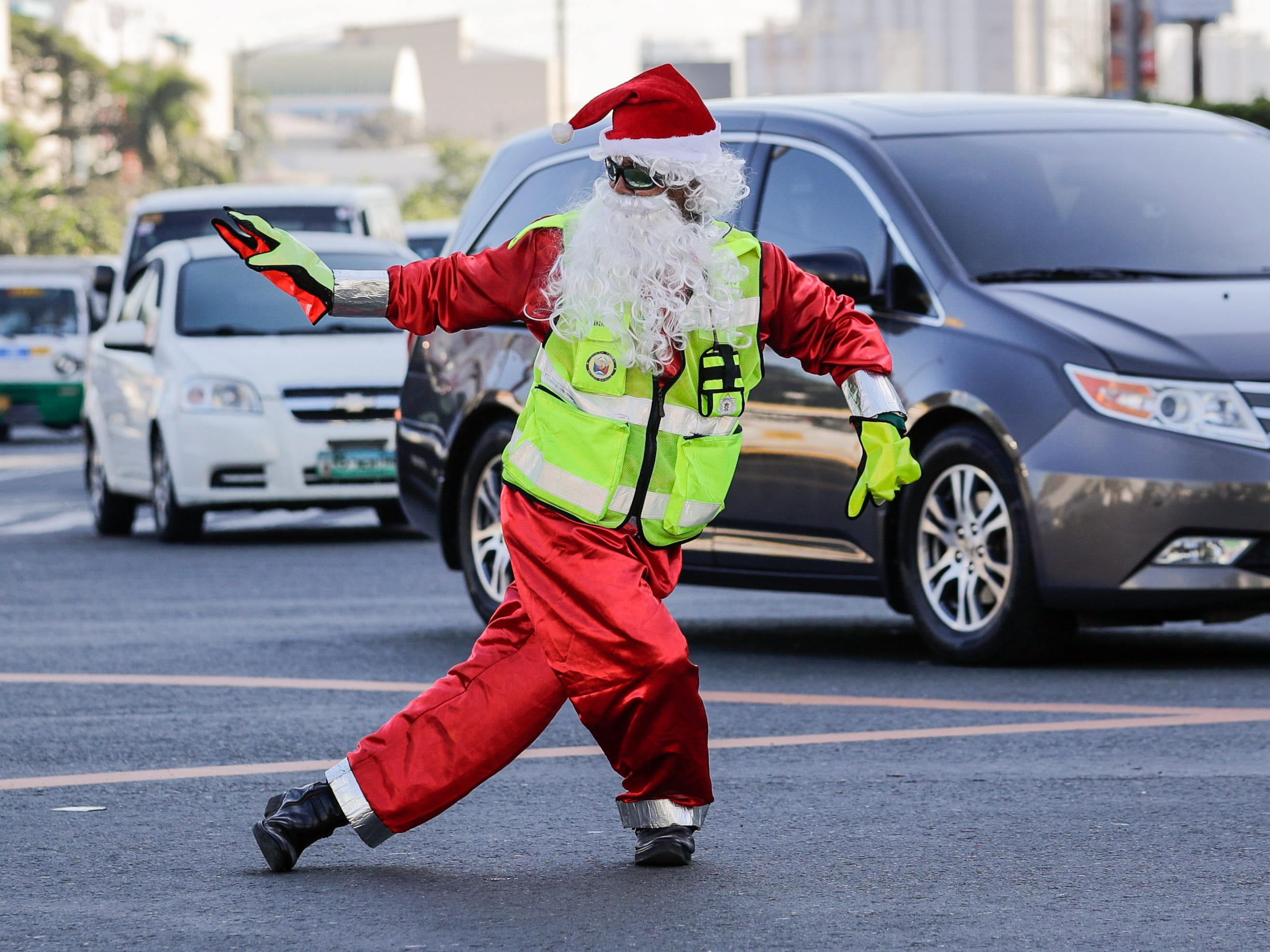 Filipino traffic officer Ramiro Hinojas, wears a Santa Claus costume, while directing traffic on a street in City of Pasay, Philippines, Dec. 12, 2018. Hinojas dances while working to make traffic more bearable at Metro Manila's busiest intersections during busy times.