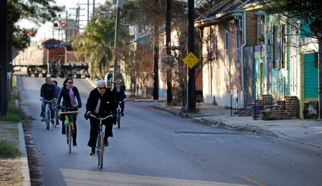 In this Feb. 13, 2015 file photo, cyclists ride along Chartres St. near the Mississippi River waterfront in the Bywater section of New Orleans. A New Orleans City Council member has released a long-awaited proposal that would ban short-term rentals of whole houses in the city's residential areas.