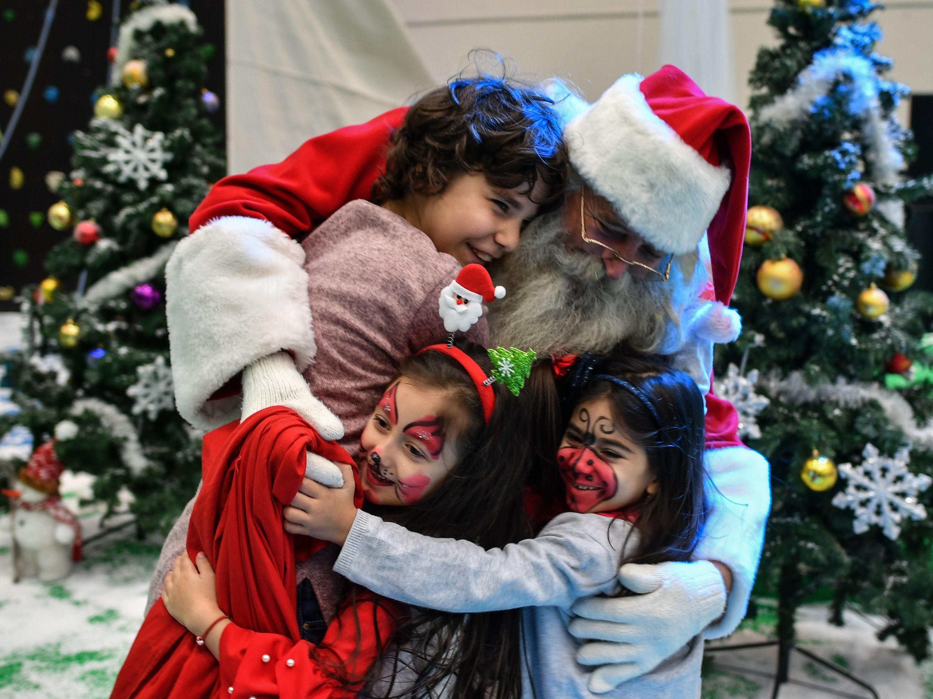 """A man dressed as Santa Claus poses with children during an event organized by the Romanian Ministry of Defense for the children of soldiers killed or injured in military action in Bucharest, Dec. 14, 2018.  During the event titled """"Christmas takes place in the great family of the Romanian Armed Forces"""", children receive gifts chosen by Santa with the Charity Association of the Romanian Army """"Camarazii"""" (""""The Brothers in Arms"""")."""
