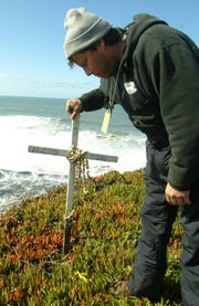 Surf videographer Eric Nelson replants a memorial cross in honor of surfer Mark Foo during the Mavericks Surf Contest in 2004, in Half Moon Bay, Calif. Foo was killed while surfing Mavericks in 1994. Mavericks is a big-wave surf spot that breaks half a mile off the coast of Half Moon Bay. Foo's name on the cross had faded, and Nelson wrote it again. This year, Mavericks' deadly wave will host women for the first time as official entrants, who will get the same prize money as men for risking their lives in the big surf.