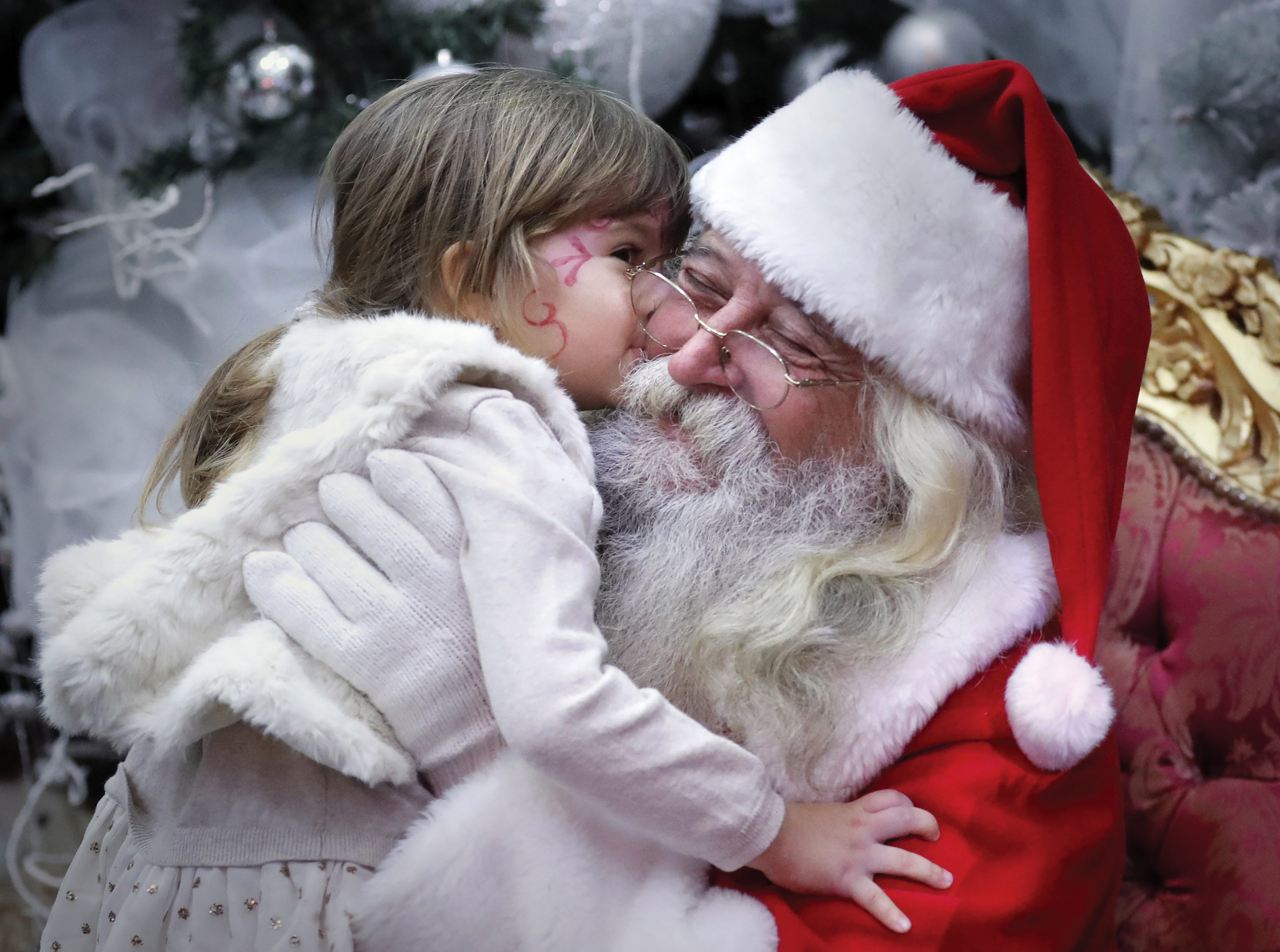 A Santa is kissed by a Romanian girl before giving her a gift while attending a Christmas Tree show dedicated to the children of the fallen or wounded soldiers of the Romanian Army, who died or got injured while serving in Afghanistan and Iraq, in Bucharest, Romania on Dec. 14, 2018. The children could play in different playground areas before receiving their Christmas gifts. The event was organized by the Ministry of Defense in collaboration with the charity association of the Romanian Armed Forces named 'Comrades'.