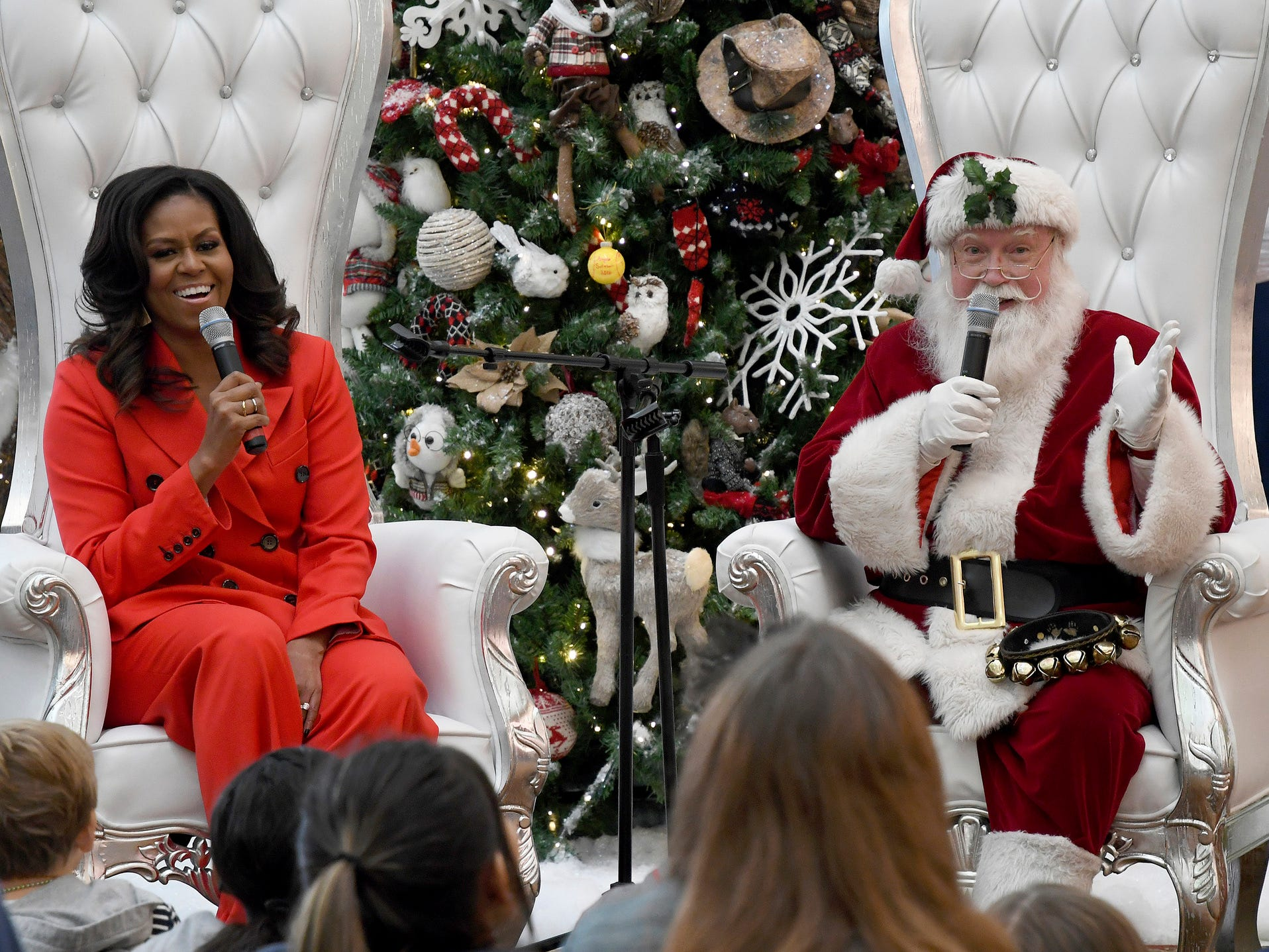 """Santa Claus and former first lady Michelle Obama answer questions after Obama read """"The Night Before Christmas"""" to a group of patients at Children's Hospital Colorado in Aurora, Colo. on Dec. 13, 2018."""