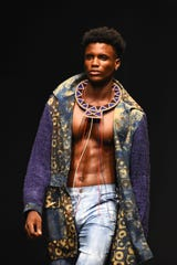 A model presents a creation by Kikoromeo on the runway during the Lagos Fashion Week