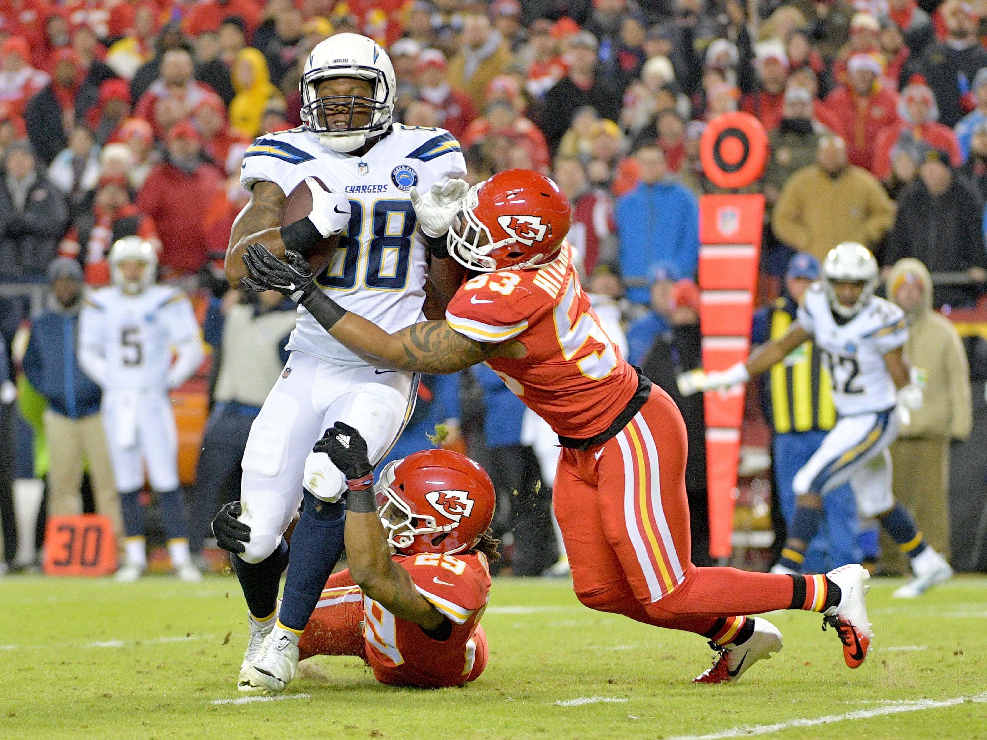 Los Angeles Chargers tight end Virgil Green (88) is tackled by Kansas City Chiefs defensive back Eric Berry (29) and inside linebacker Anthony Hitchens (53) during the first half at Arrowhead Stadium.