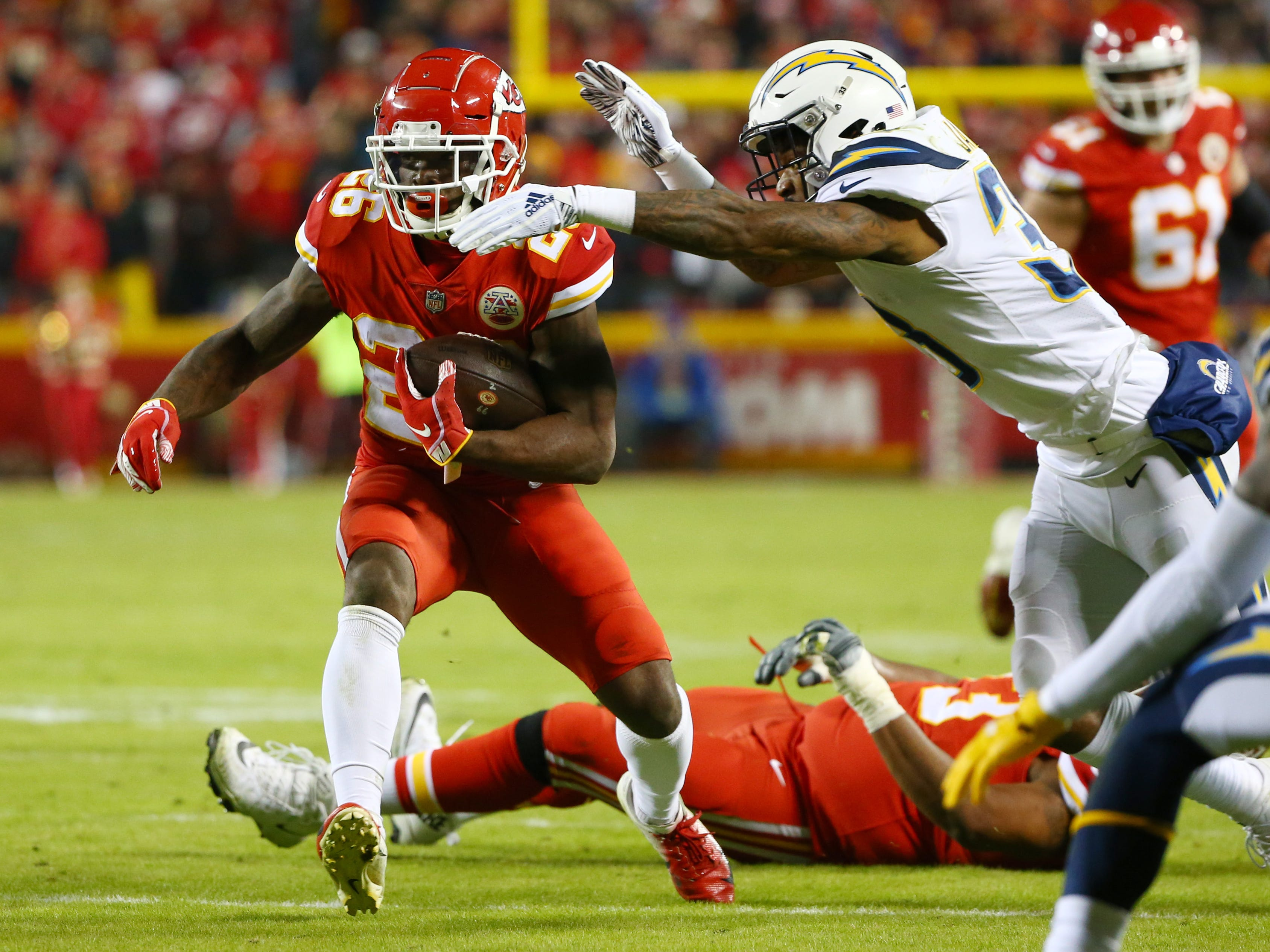 Kansas City Chiefs running back Damien Williams (26) is tackled by Los Angeles Chargers safety Derwin James (33) in the first half at Arrowhead Stadium.