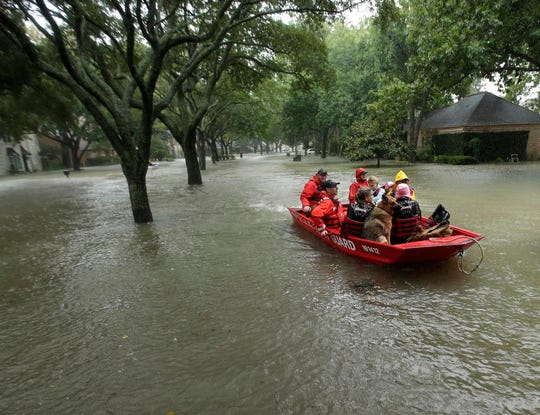 A Coast Guard rescue team evacuates people from a neighborhood inundated by floodwaters from Tropical Storm Harvey in Houston.