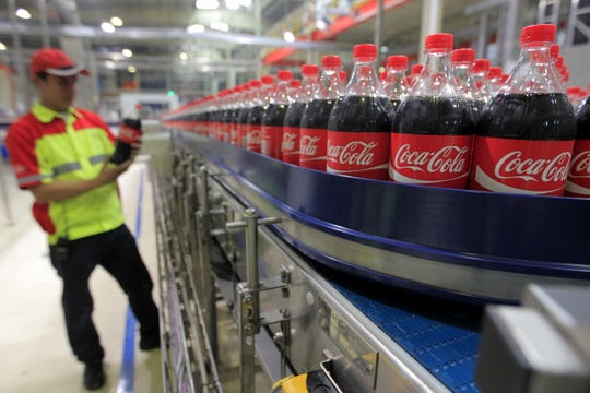 epa07130774 (FILE) A file photo dated 31 March 2015 showing an Indonesian worker standing next to Coca-Cola products in the Coca Cola Amatil Indonesia (CCAI) Cikekodan Plant in Bekasi, West Java, Indonesia (reissued 30 October 2018). The Coca-Cola Company, the world's largest beverage company, is to release their 2018 3rd quarter earnings results on 30 October 2018.  EPA-EFE/BAGUS INDAHONO ORG XMIT: BGS83