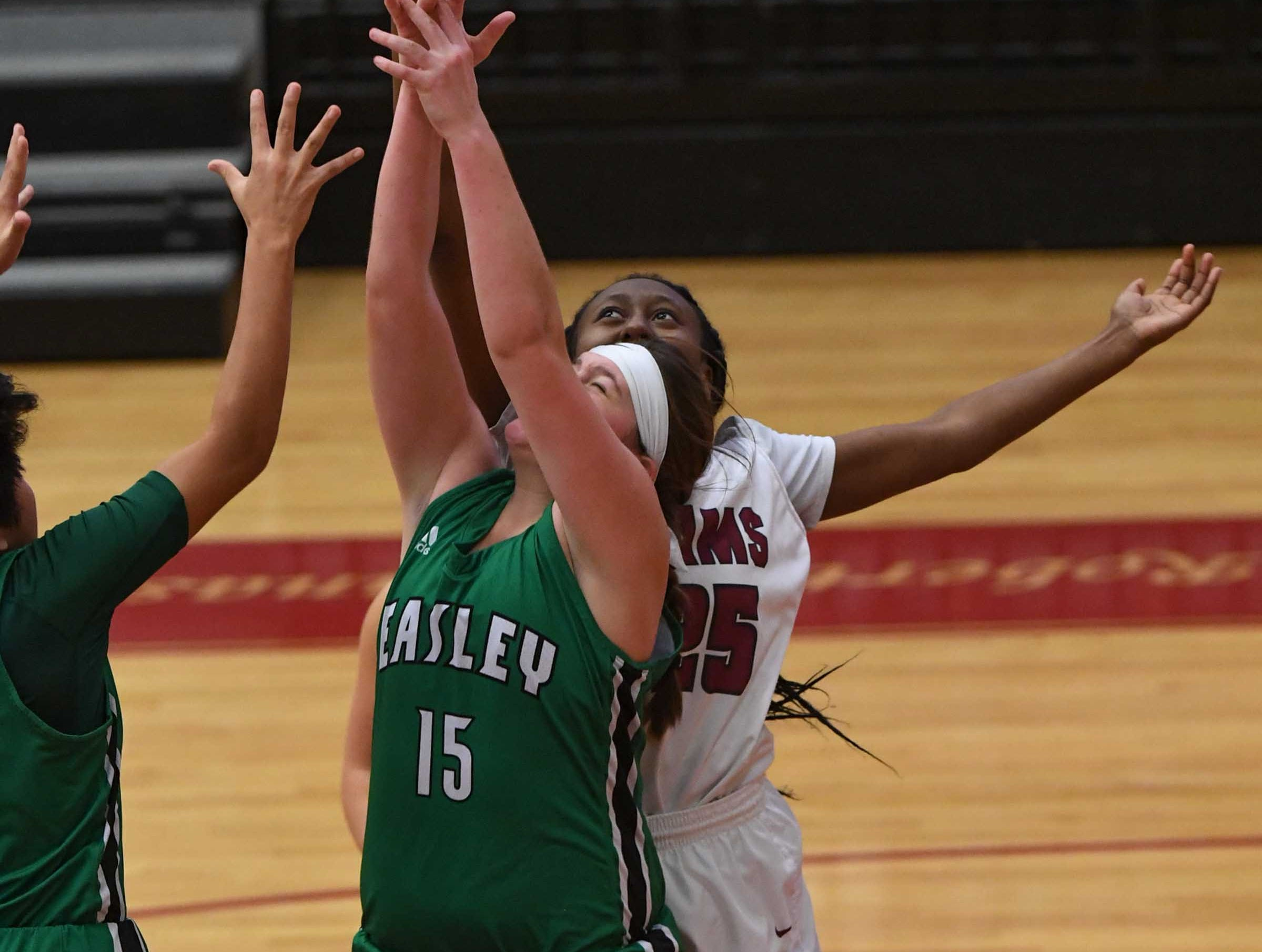 Westside junior Keyshuna Fair(25) and Easley freshman Kylie Nabors(15) reach for a ball during the third quarter at Westside High School in Anderson on Friday.