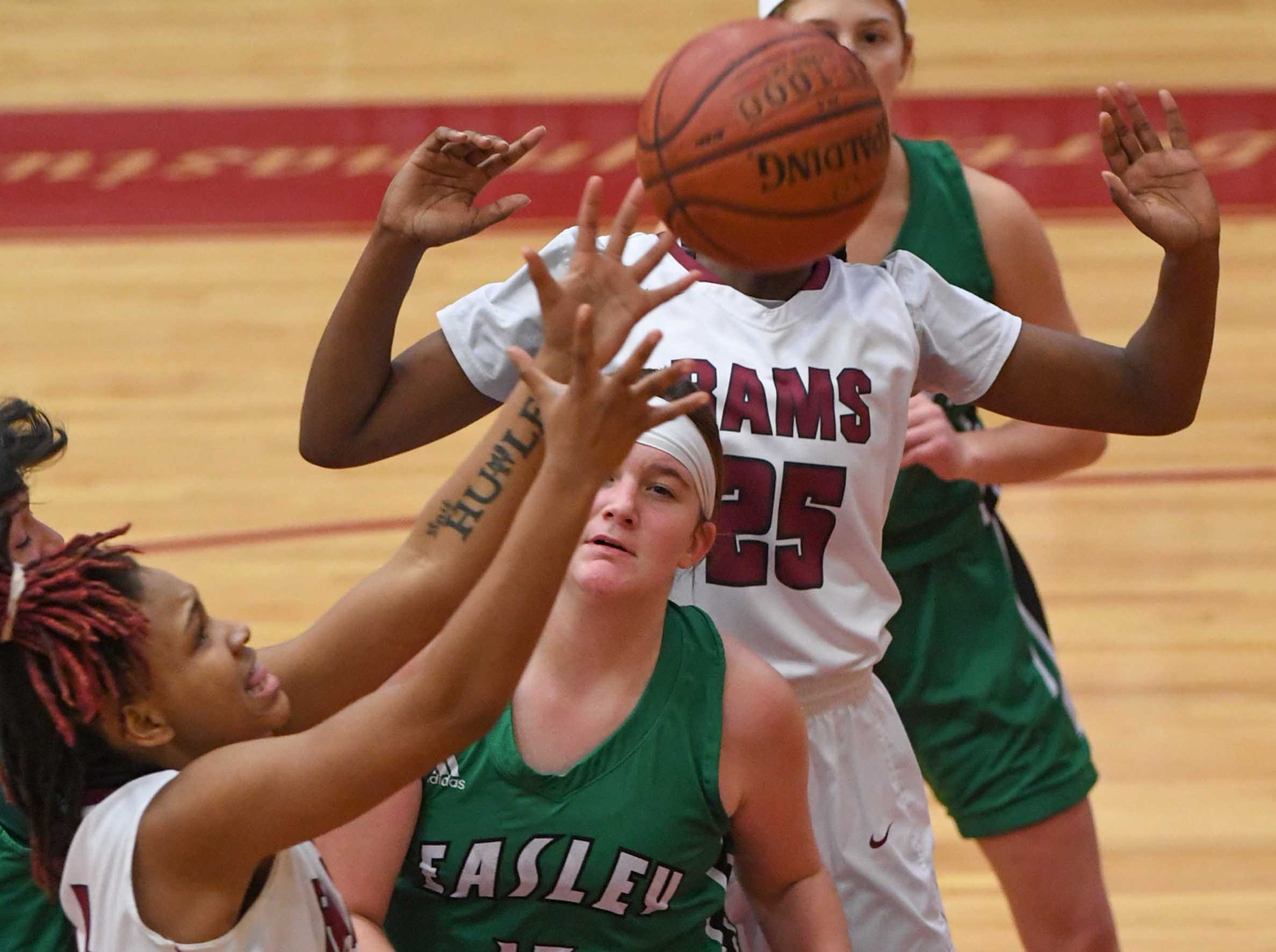 Westside freshman Aziyah Bell(4) reaches for a loose ball near teammate Westside junior Keyshuna Fair(25) and Easley freshman Kylie Nabors(15) during the third quarter at Westside High School in Anderson on Friday.