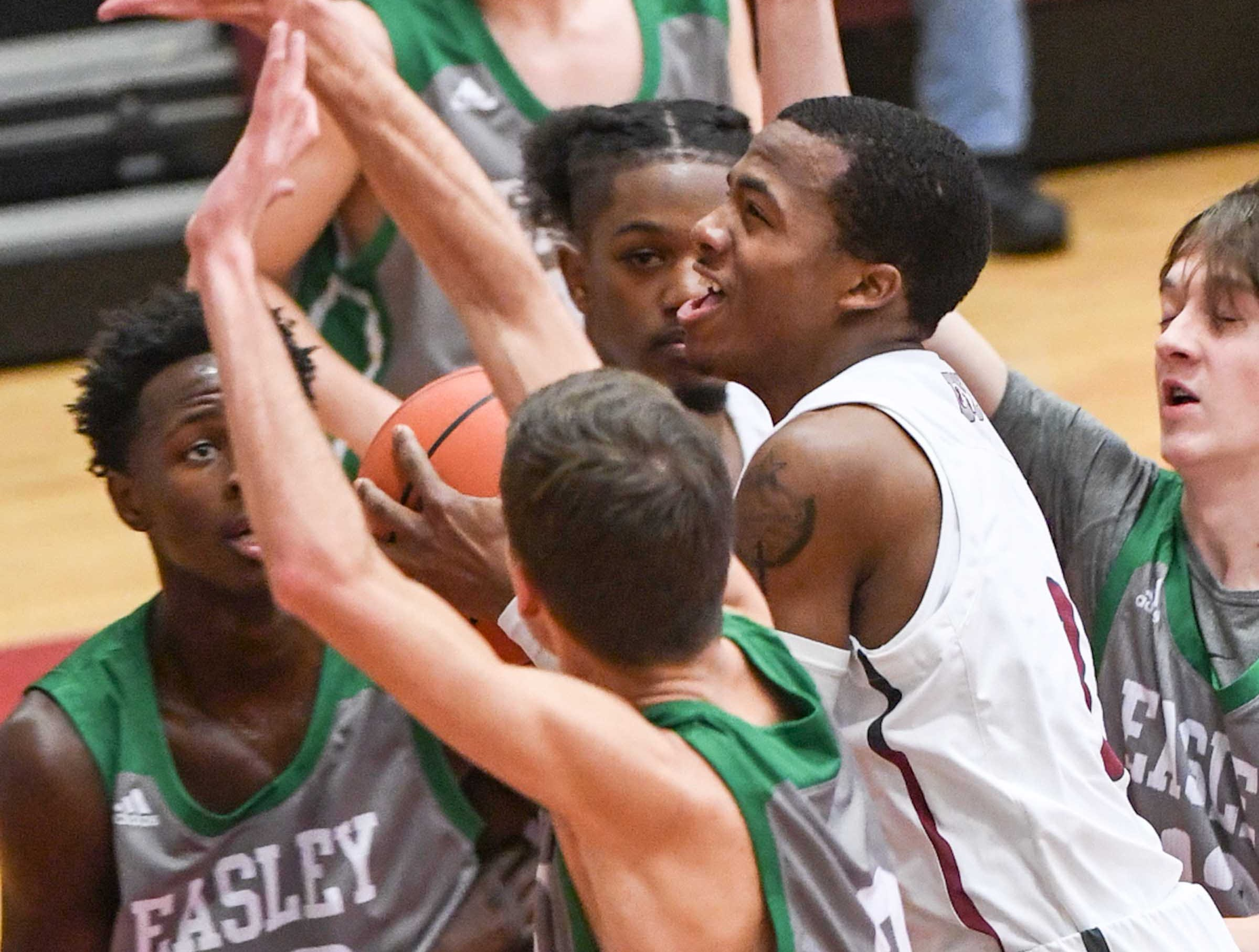 Westside senior Traye Carson(3) shoots between Easley junior Jaquan Sanders(22) and Easley senior Griffin Smith(3) for his 1,000th point during the first quarter at Westside High School in Anderson on Friday.