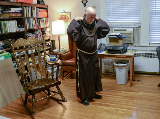 Father Bob Menard, campus chaplain at Saint Andrew Catholic Church in Clemson, puts on his robe at the student center building in Clemson.
