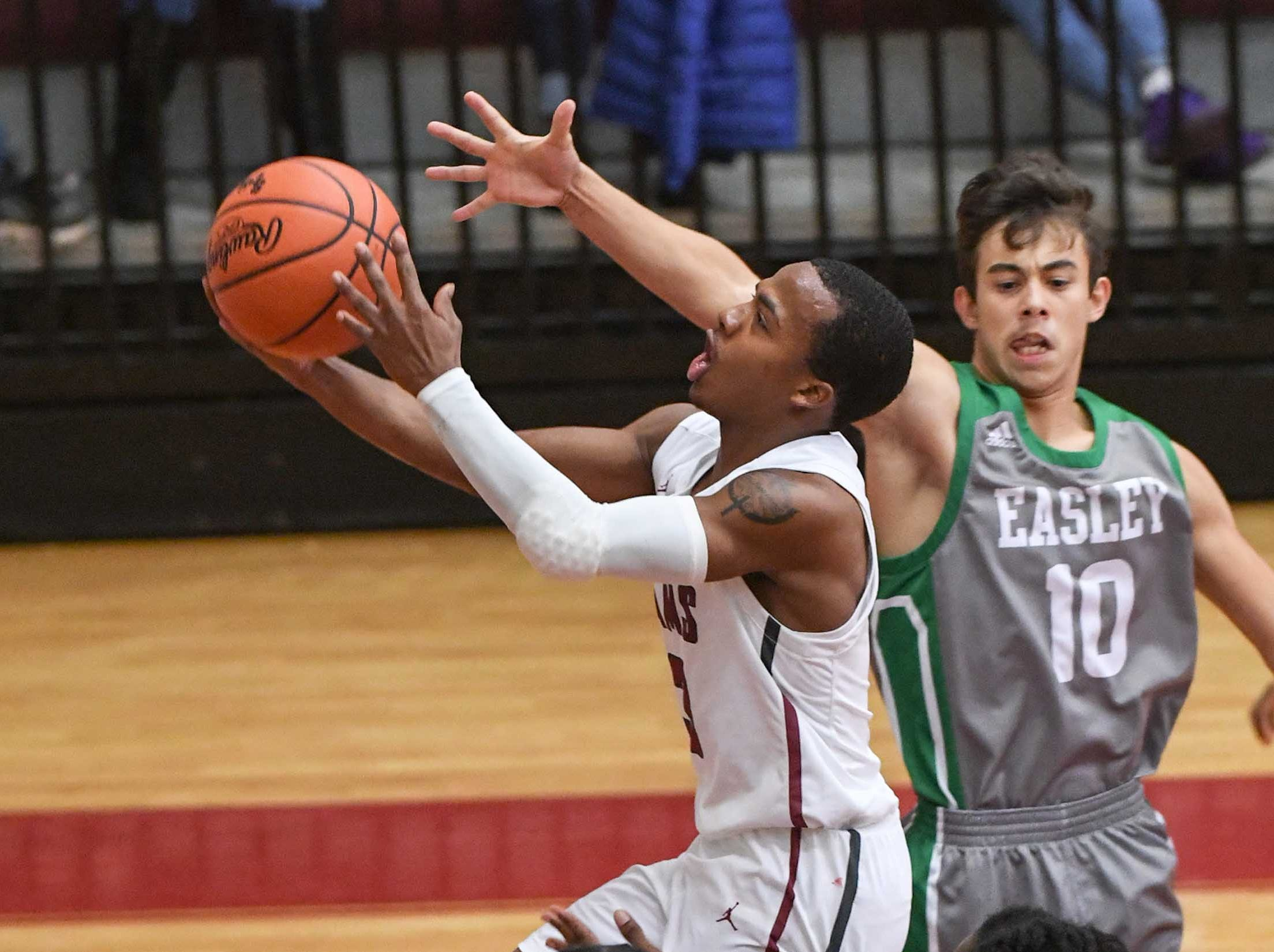 Westside senior Traye Carson(3) shoots around Easley junior Malaki Calhoun(10) during the first quarter at Westside High School in Anderson on Friday.