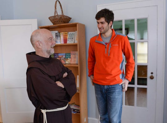 Father Bob Menard, left, campus chaplain at Saint Andrew  Catholic Church in Clemson, talks with James Jolly, right, at the student center building in Clemson.