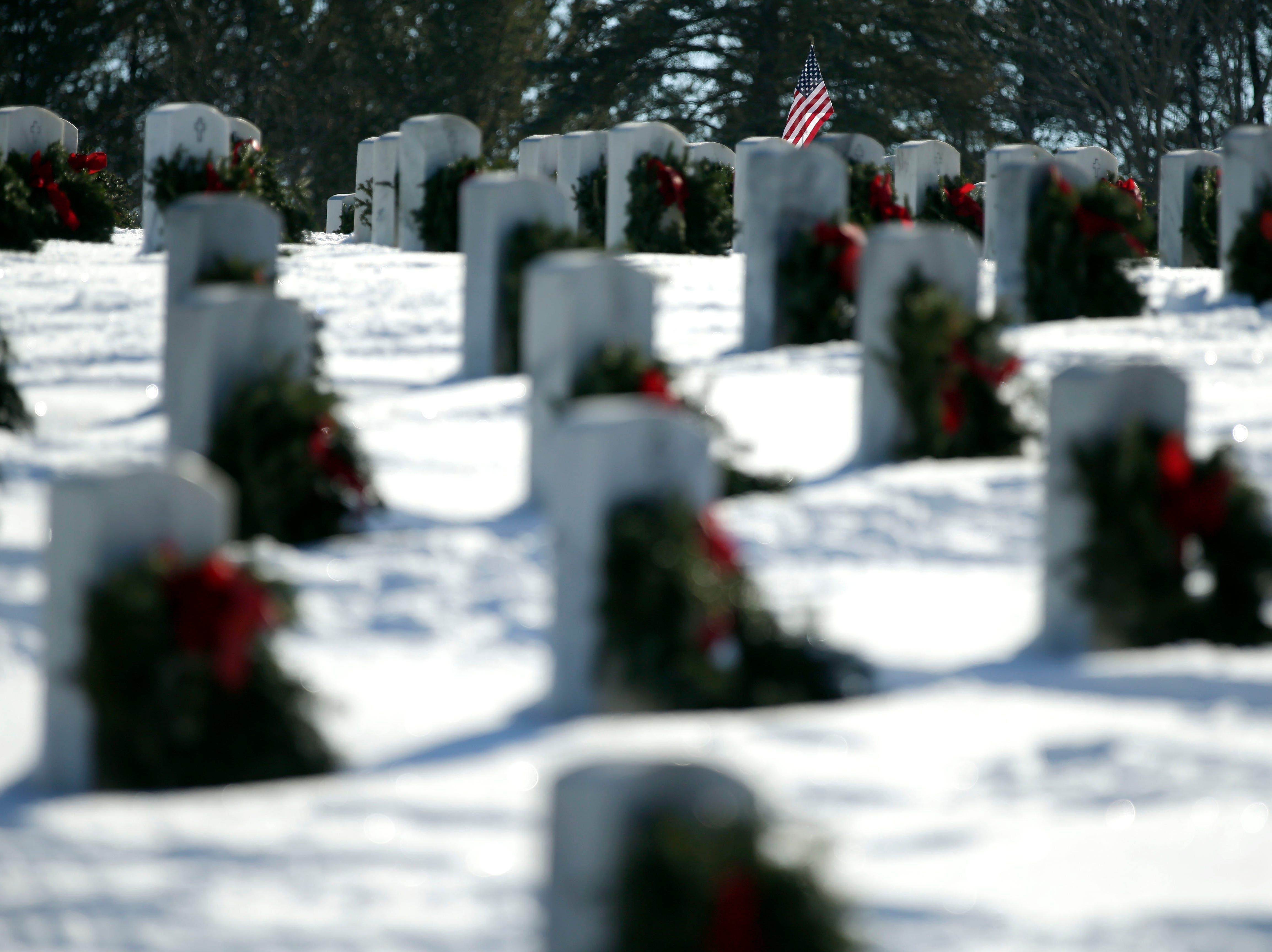 A flag stands among headstones decorated with wreaths after volunteers took part in Wreaths Across America Day at the Central Wisconsin Veterans Memorial Cemetery Saturday, December 15, 2018, in King, Wis. Over 7000 graves at King were honored with wreaths. Over 1400 other locations took part in the coordinated ceremony.