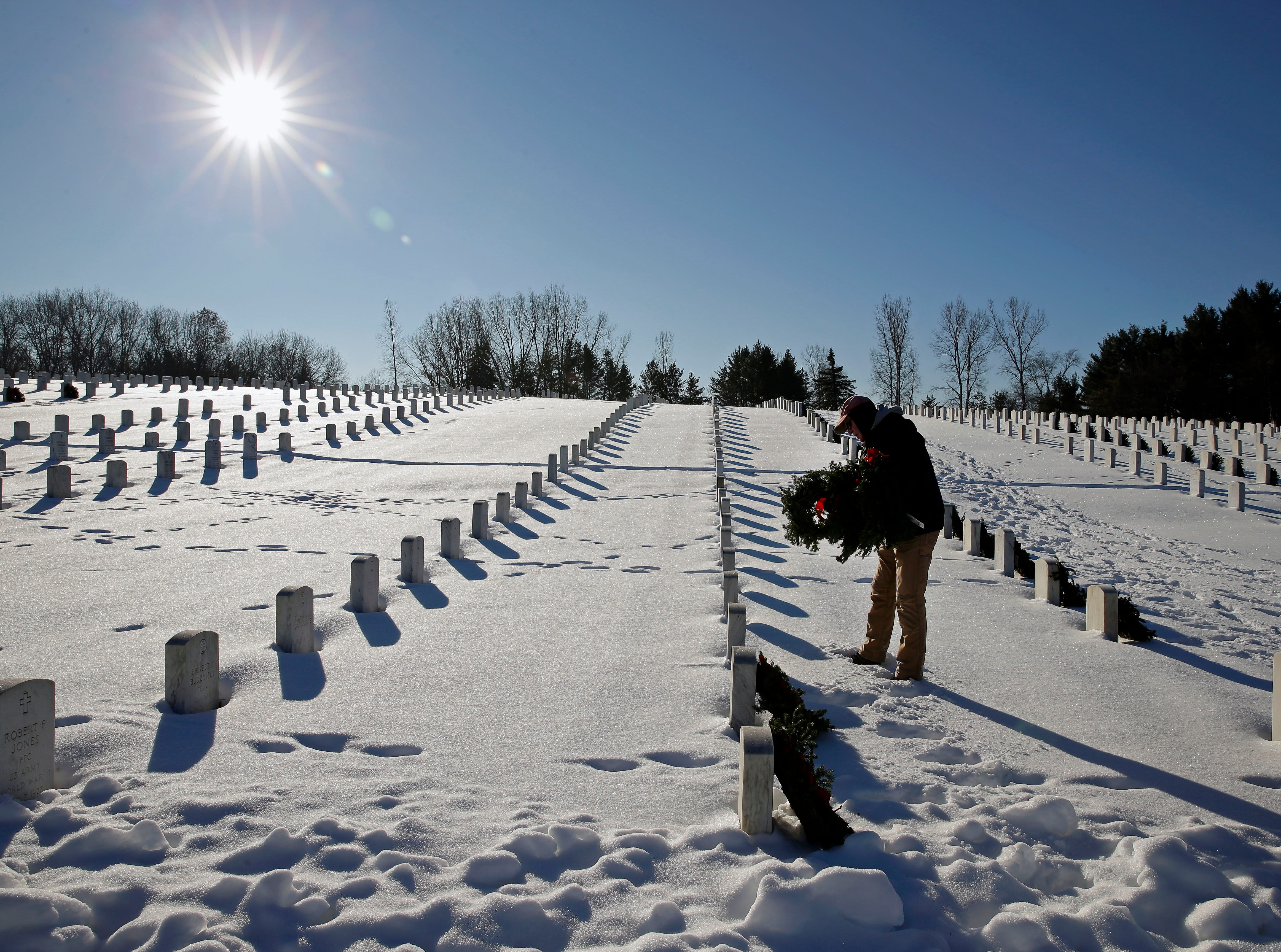 Dave Larson of Waupaca places wreaths as he joins other volunteers taking part in Wreaths Across America Day at the Central Wisconsin Veterans Memorial Cemetery Saturday, December 15, 2018, in King, Wis. Over 7000 graves at King were honored with wreaths. Over 1400 other locations took part in the coordinated ceremony.