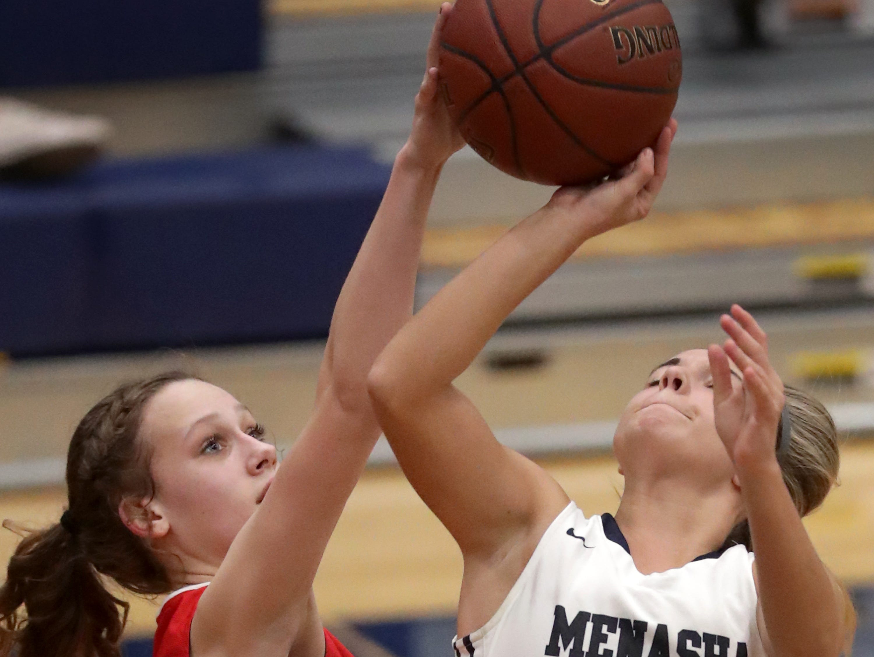 New London High School's #23 BreAnna Hacker against Menasha High School's #12 Katelyn Roesler during their girls basketball game on Friday, December 14, 2018, in Menasha, Wis.