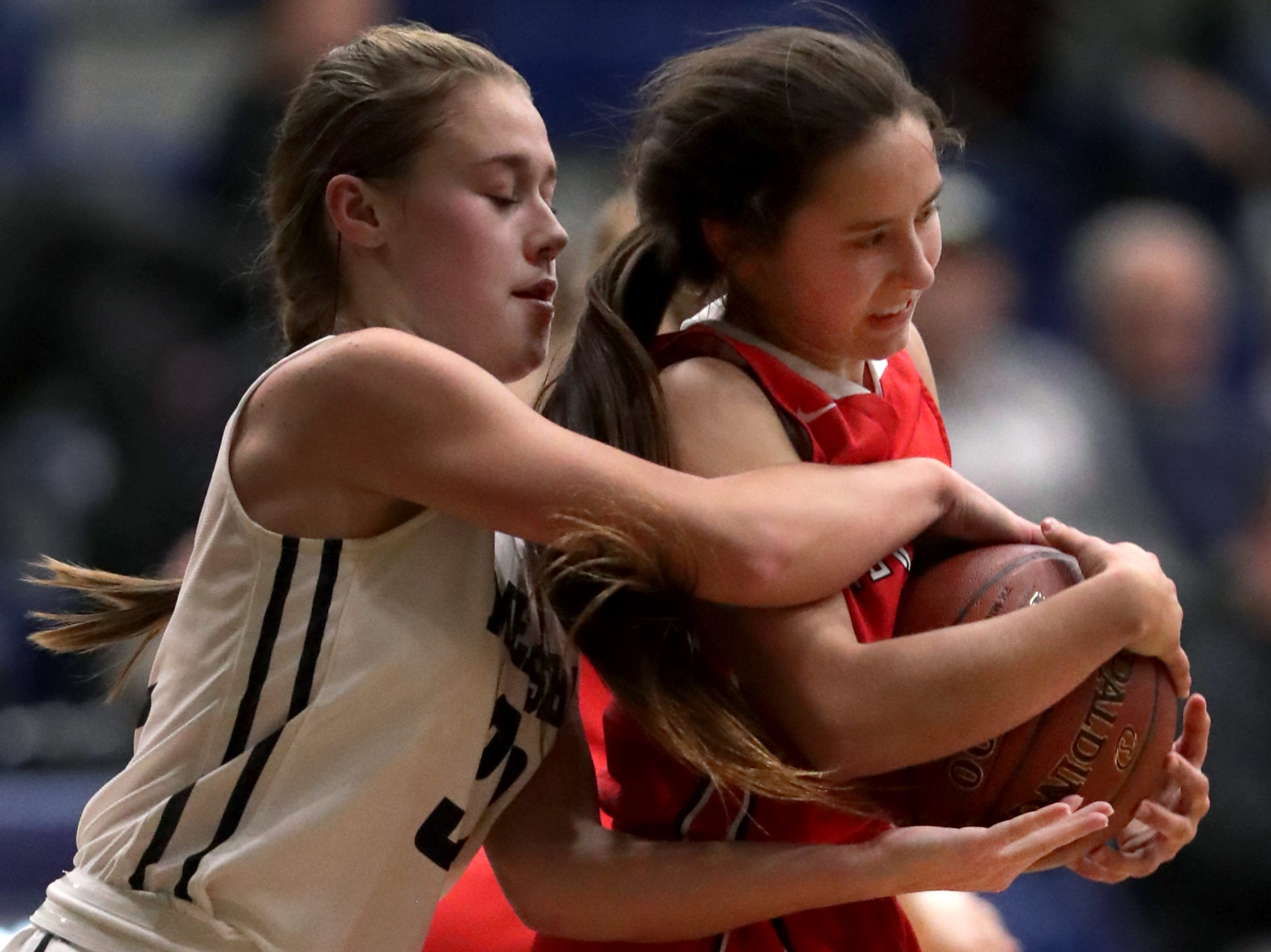 New London High School's #24 Samantha Pfefferle against Menasha High School's #32 Leah Johnson during their girls basketball game on Friday, December 14, 2018, in Menasha, Wis.