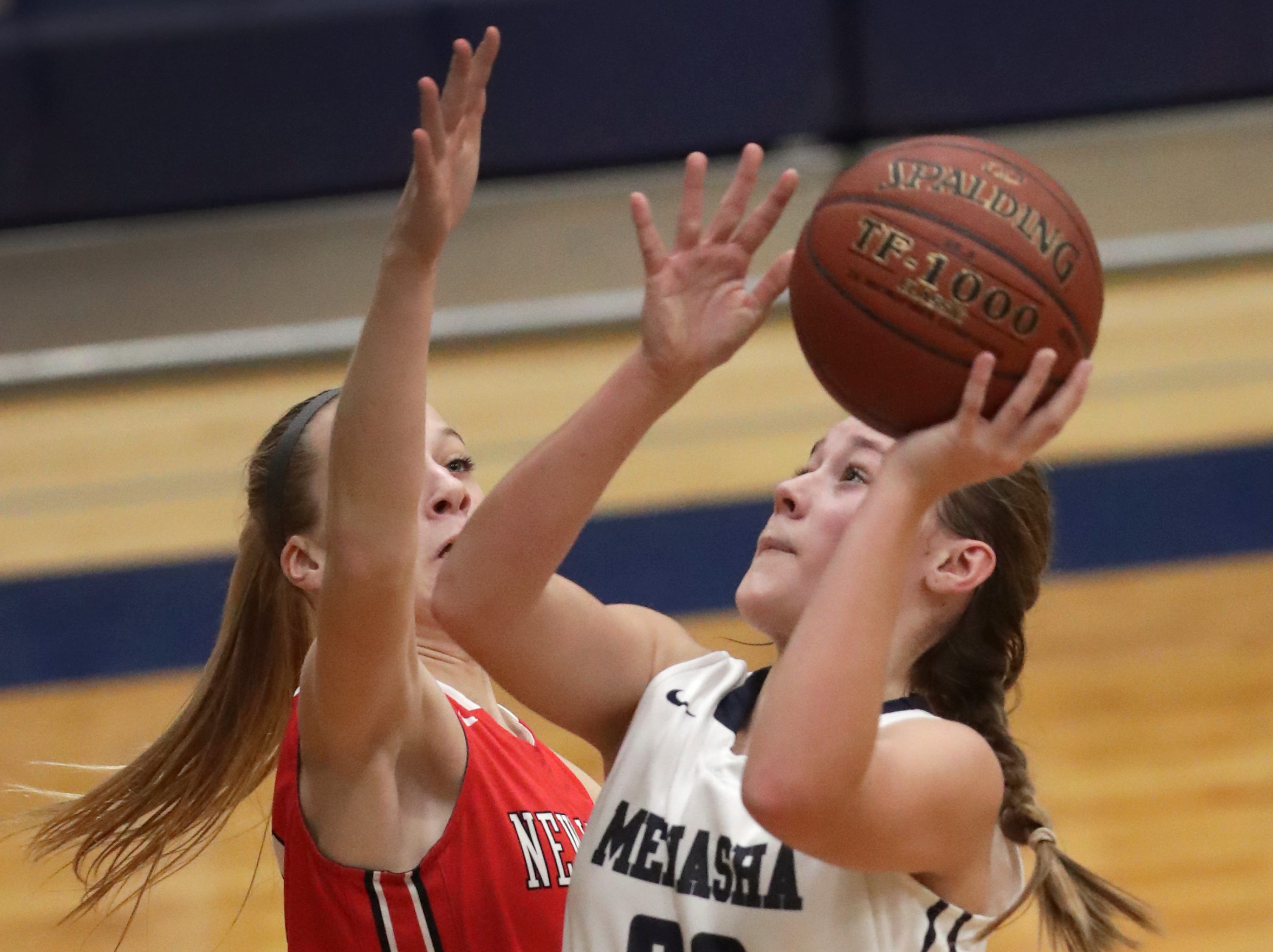 New London High School's #11 Megan Pankow against Menasha High School's #32 Leah Johnson during their girls basketball game on Friday, December 14, 2018, in Menasha, Wis.