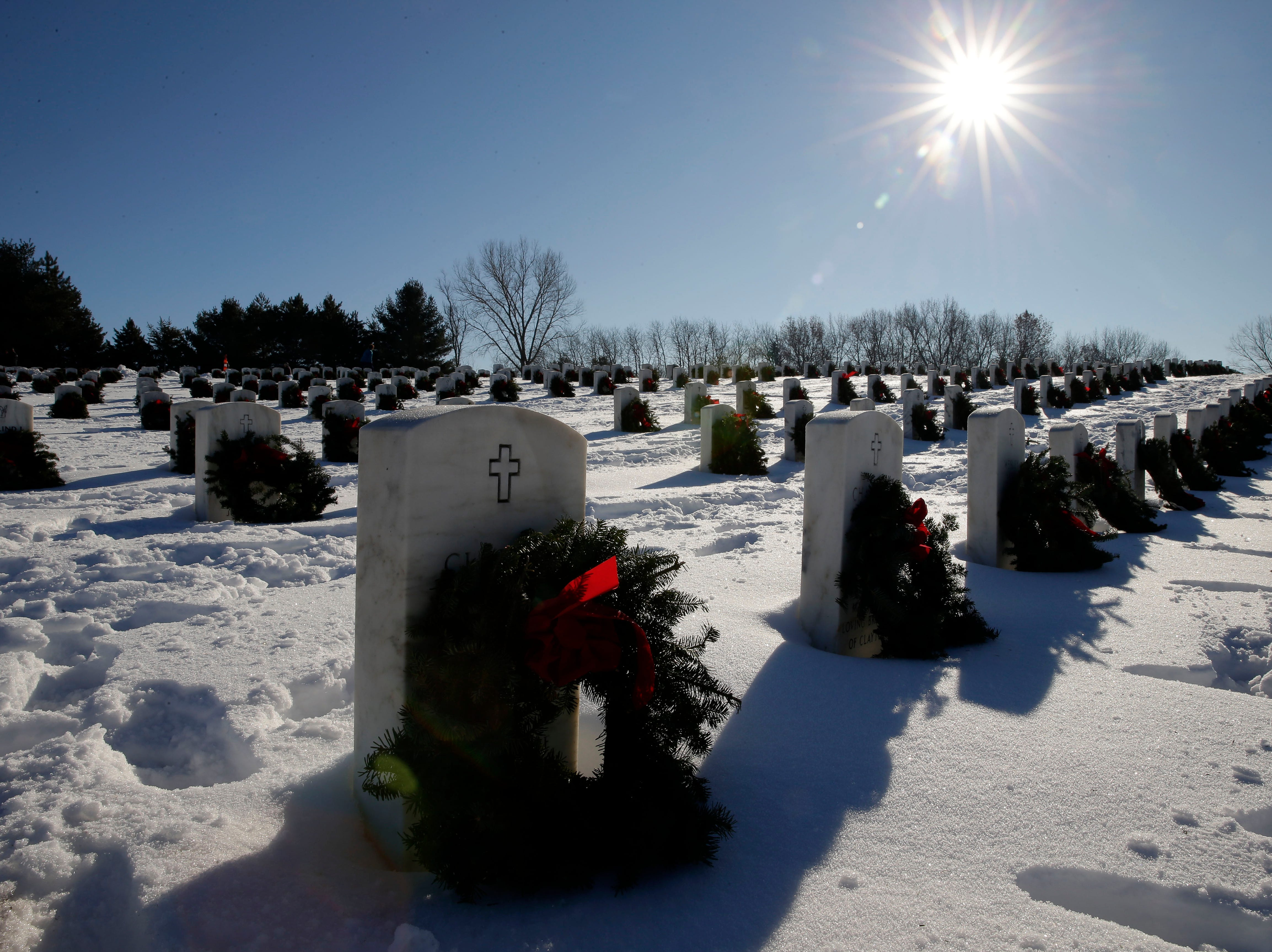 Wreaths are placed at graves during Wreaths Across America Day at the Central Wisconsin Veterans Memorial Cemetery Saturday, Dec. 15, 2018, in King, Wis. More than 7,000 graves at King were honored with wreaths. Over 1,400 other locations took part in the coordinated ceremony.
